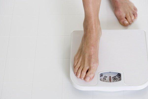 Девушка наступает на весы